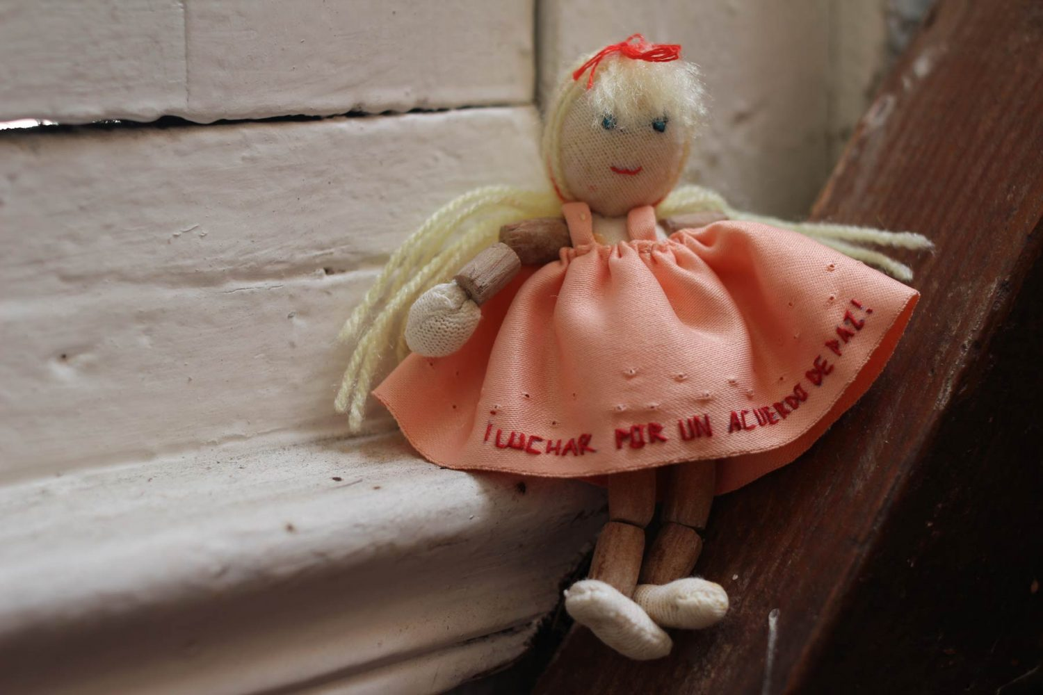 """Doll made of recycled threads, textiles and wood. Embroidery reads: """"Fighting for a peace agreement"""", approx. 1999"""