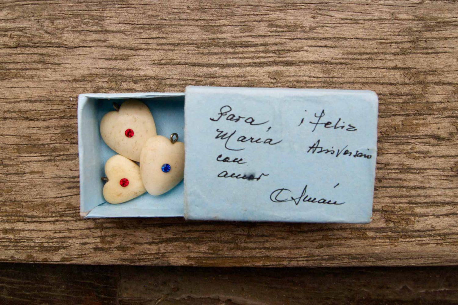 """Blue wrapped matchbox with three heart-shaped pendants carved out of bovine bone with glitter jewellery. Box reads: """"Sara Maria, Happy Anniversary. With love C. Juan"""", approx. 1998"""